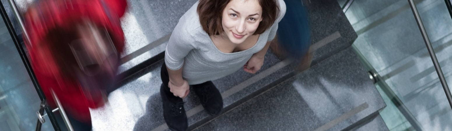 Woman on busy school staircase looking up to camera